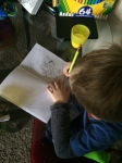 Finishing our homework. I helped a bit with the drawings for his story.